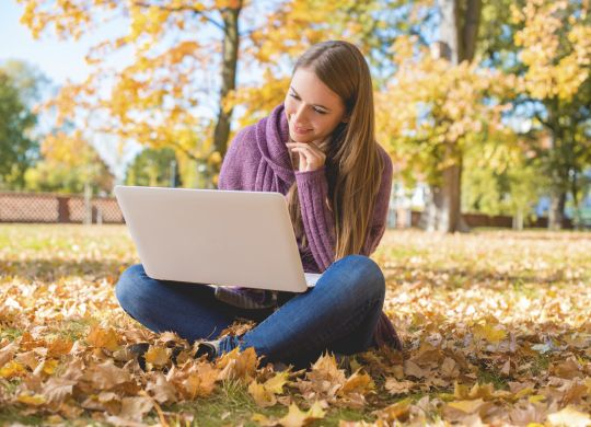 Smiling Woman Using Laptop Sitting on Ground Alone