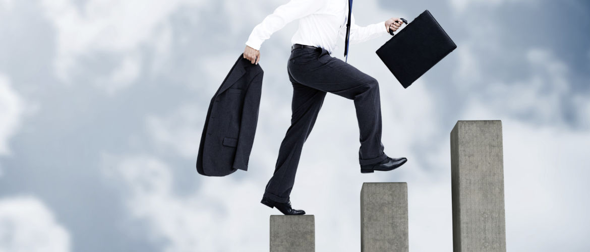 Young businessman climbing grey steps on sky background