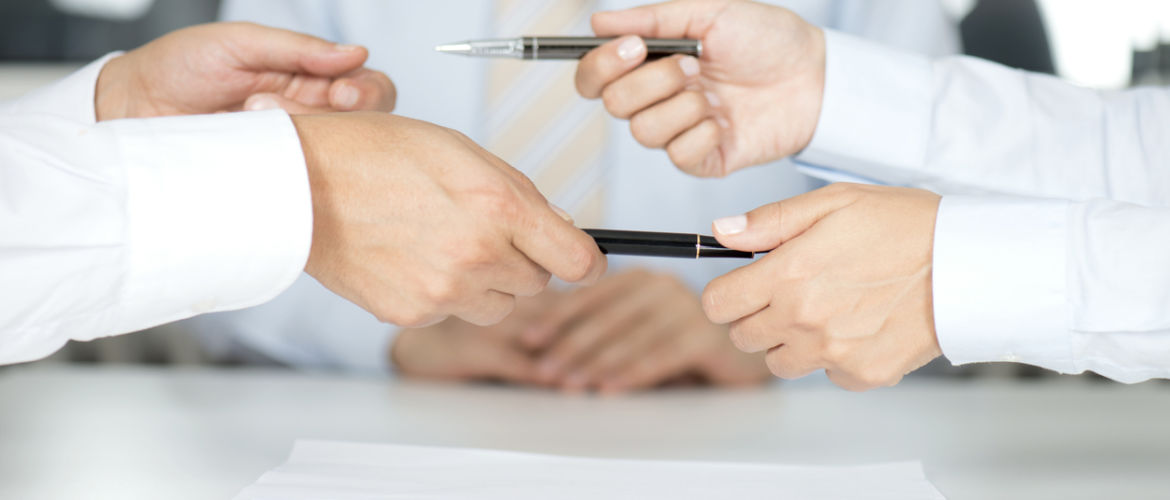Two men are giving each other their pens after signing contract paper, horizontal