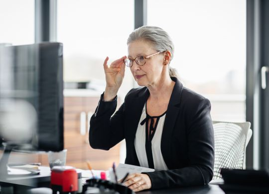 Portrait of a senior businesswoman sitting on her desk in a modern office and. She's working on a computer and wearing glasses and has silver hair.