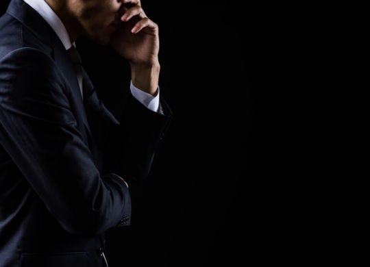 This is a photograph of a depressed businessman on black background