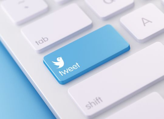 High quality 3d render of a modern keyboard with tweet button on a blue background and copy space. The tweet keyboard button has a text  and an icon on it. The tweet keyboard button is  in focus, Horizontal composition with copy space.