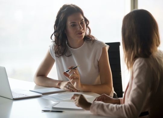 Two diverse serious businesswomen discussing business project working together in office, serious female advisor and client talking at meeting, focused executive colleagues brainstorm sharing ideas (Two diverse serious businesswomen discussing busines